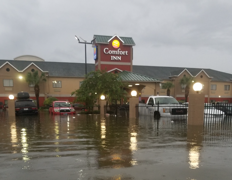 Floodwaters surround cars and the Comfort Inn, Cleveland Texas